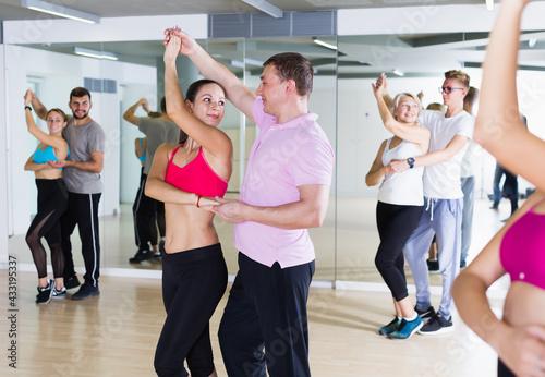 Obraz na plátně Positive dancing pair dance waltz together in studio