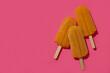 Leinwandbild Motiv Mango or caramel ice cream sticks on pink background