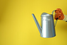 Hand In Glove Hold Watering Can On Yellow Background