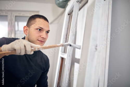 Fototapeta Young adult man painting on a DIY budget renovation of his new home apartment. obraz