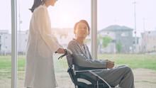 車椅子に乗った患者を励ます医師