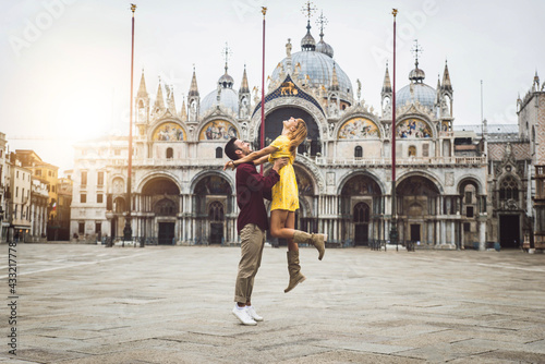 Couple of tourists visiting Venice, Italy - Boyfriend and girlfriend in love having fun on city street at sunset - People, love and holidays concept - fototapety na wymiar