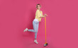 Leinwandbild Motiv Young housewife with broom on pink background