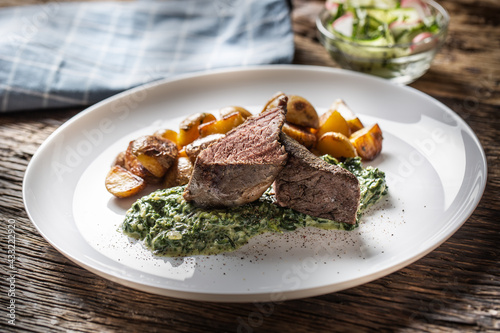 Fototapeta Delicious grilled beef sous vide steak served on a white plate with crunchy roasted potatoes, spinach dip and fresh leaf lettuce salad obraz