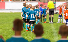 Group Of Children Soccer Players Walking On Field Before The Match. Two Opposing Youth Football Teams In Lines Before The Final Tournament Game. Teams In Red And Blue Shirts