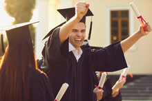 Happy Smiling University Graduate In Mantle Holding Diploma In Raised Hand And Expressing Happiness Over University Building At Background. Successful Graduating From University Or College