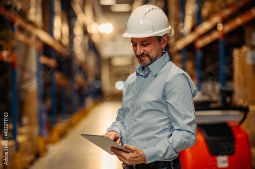 Photo Mid adult manager using digital tablet in warehouse