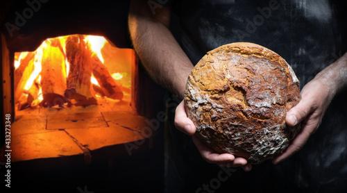 Fotografia Baker's hands holding and presenting fresh baked loaf of bread
