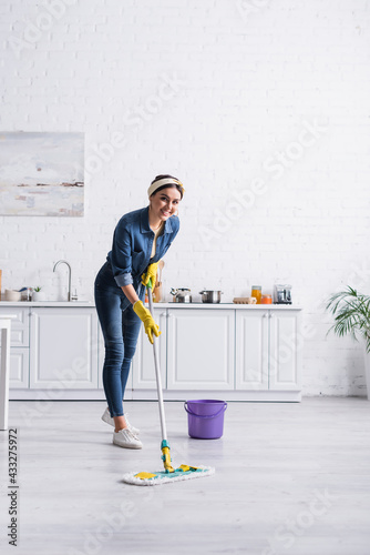Fototapeta Happy housewife cleaning floor with mop in kitchen obraz