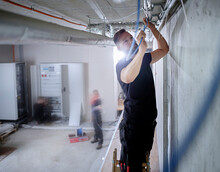 Male Electrician Installing Cables On Ceiling In While Working In Workshop