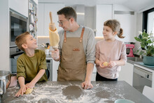 Father Showing Dough On Rolling Pin To Son While Standing By Daughter At Home