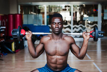 Shirtless Young Male Athlete Exercising With Barbell During Strength Training In Health Club