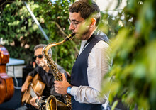 Man Playing Saxophone While Performing At Event