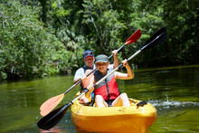 Smiling Girl With Father Canoeing With Oar In Lake