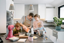 Mid Adult Man Pouring Flour In Bowl While Standing With Children At Home