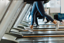 Male And Female Athlete Exercising On Treadmill In Gym
