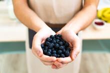Man Holding Fresh Blueberries In Kitchen