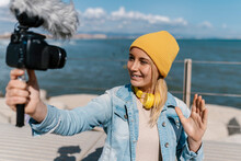Smiling Woman In Knit Hat Waving Hand While Vlogging Through Camera During Weekend