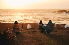 Back View Of Three Unrecognizable People Keeping A Safe Distance While Watching A Beautiful Sunset Over The Sea.