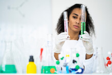 Young Female Researcher Analyzing Test Tubes In Laboratory
