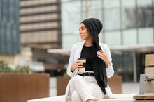 Woman Holding Headscarf Having Coffee While Sitting Outdoors