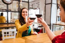 Happy Female Friends Toasting Glasses Of Wine At Table In Bar