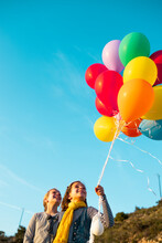 Cheerful Girls Playing With Colorful Helium Balloons