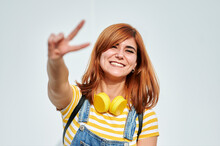 Smiling Redhead Woman Gesturing Peace Sign In Front Of White Wall
