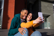 Young Man Making Face While Girlfriend Taking Selfie Through Smart Phone