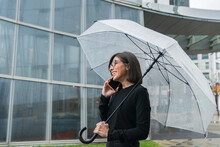 Cheerful Young Woman Holding Umbrella While Talking On Phone By Glass Building During Rain