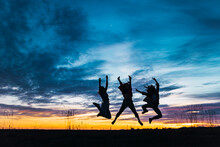 Carefree Female Friends With Arms Raised Jumping In Front Of Sky