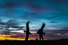 Female Friends With Skateboards Tossing Hair During Sunset