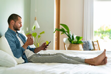 Young Man With Coffee Cup Using Smart Phone At Home