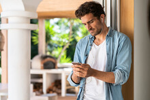 Serious Man With Headphones Using Smart Phone While Leaning On Doorframe