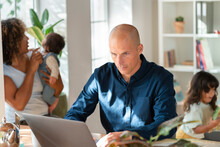 Father Working On Laptop While Family Running In Background At Home Office