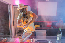 Man Coocking French Fries With Gas Mask In Food Truck;Steam;Smoke;Heat;