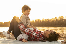 Playful Mother And Son Looking At Each Other By Lake During Sunset