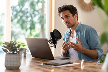 Male Freelance Worker Looking Away While Podcasting At Home Office