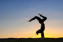 Young Woman In Silhouette Doing Handstand During Sunset