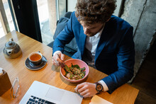 Businessman Having Salad While Sitting With Laptop At Cafe