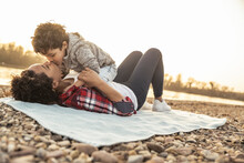 Boy Kissing Mother Lying On Blanket Over Pebbles During Sunset