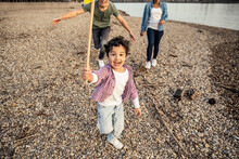 Playful Boy Holding Sticks While Playing With Parents In Background Over Pebble