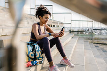 Female Athlete Using Mobile Phone While Sitting On Staircase