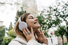 Happy Young Woman Listening Music On Headphones Outdoors