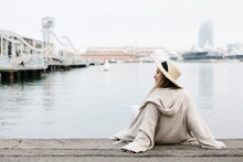 Young Woman Wearing Hat Relaxing On Retaining Wall At The Waterfront