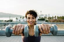 Smiling Female Athlete With Headphones Holding Dumbbells