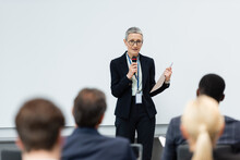 Mature Speaker With Paper Folder Talking Near Blurred Business People During Meeting