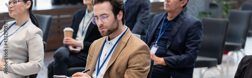 Fotografie, Obraz Young businessman writing on notebook near blurred interracial colleagues in con