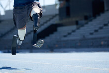 Male Amputee Athlete Sprinting On Sunny Blue Sports Track