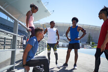 Runner And Amputee Friends Talking On Sunny Sports Track
